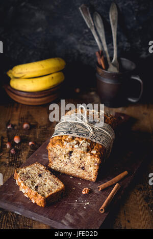 Banana bread with walnuts, cinnamon and chocolate chips on wooden cutting board. Selective focus. Food still life, - Stock Photo