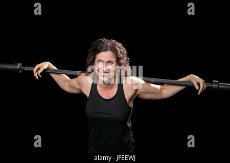 A female weight lifter relaxes with arms stretched out over a barbell that is across her shoulders.  She smiles - Stock Photo