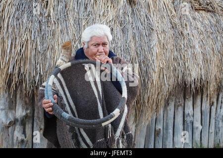 Chile, Araucania, Llaguepulli, Mapuche, Ruka, round house, man, traditional costume, wind instrument, - Stock Photo