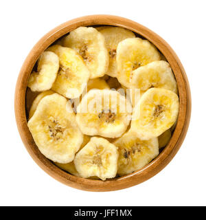 Dried banana chips in wooden bowl. Yellow deep fried slices of bananas, covered with sugar or honey. Snack with - Stock Photo