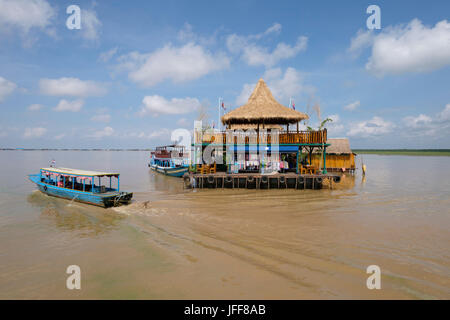 Boat next to a building on a floating village in the Mekong river, Cambodia