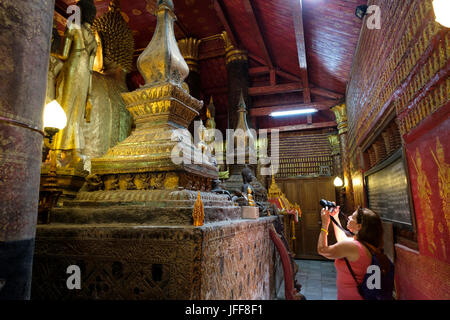 Tourist taking pictures inside the Wat Mai Suwannaphumaham (aka Vat May) buddhist temple in Luang Prabang, Laos, - Stock Photo