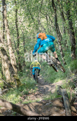 Biker jumping in mid-air while riding bike and following other biker on dirt path - Stock Photo