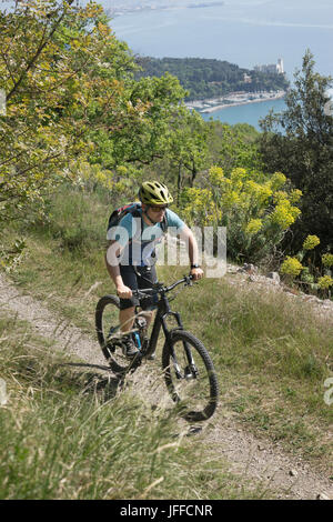 Mature biker riding bike on trails through dirt road - Stock Photo
