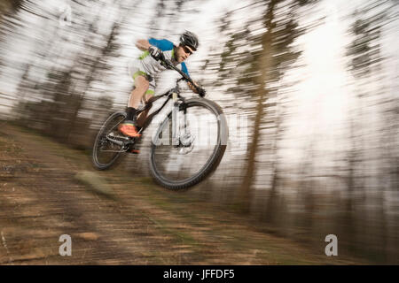Mountain biker performing stunt in forest - Stock Photo