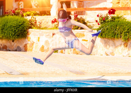 Joyful girl jumping to the pool, cute little child wearing goggles and flippers for diving, happy carefree childhood, - Stock Photo