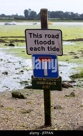 Flood warning sign on the coast road beside the harbour in the famous town of Bosham where King canute commanded - Stock Photo