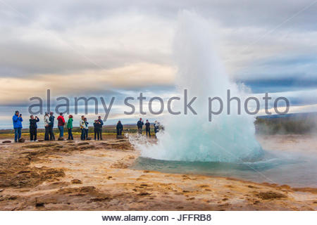 Tourists watching the Strokkur fountain geyser erupt in the Haukadalur geothermal area. - Stock Photo