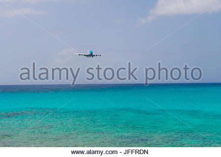 A jumbo jet airplane flying low over the Atlantic Ocean before landing at Princess Juliana Airport. - Stock Photo