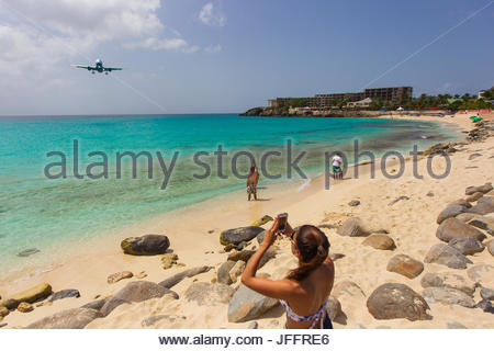 A jumbo jet airplane flying low over the water at Maho Beach before landing at Princess Juliana Airport. - Stock Photo