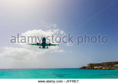A jumbo jet airplane flying low over the Atlantic Ocean just before landing at Princess Juliana Airport. - Stock Photo