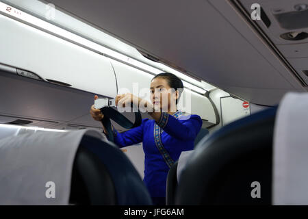 Flight hostess in uniform showing how to use the airplane seat belt during safety procedures - Stock Photo