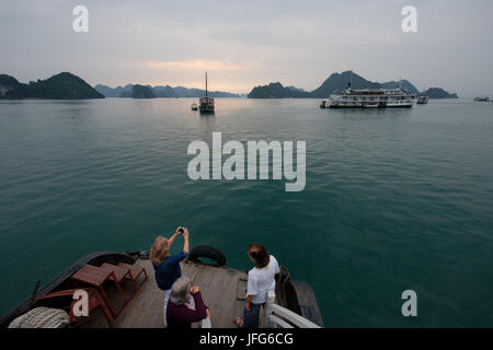 Tourists taking picture on the deck of a cruise tour boat on Halong Bay, Vietnam, Asia - Stock Photo