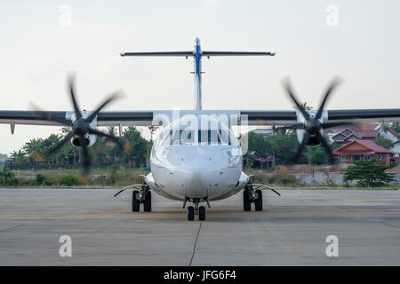 Frontal view of a twin engine propeller airplane on an airport tarmac - Stock Photo