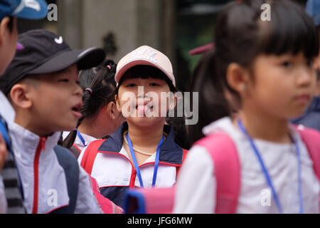Asian boy sticking his tongue out among other young children during a school day trip - Stock Photo
