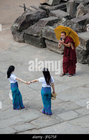 Buddhist monk taking pictures of two girls on holidays using his smartphone while visiting Angkor Wat temple complex - Stock Photo