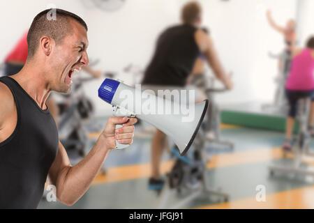 Composite image of irritated male trainer yelling through megaphone - Stock Photo