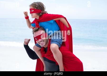Father and son in superhero costume pretending to run - Stock Photo