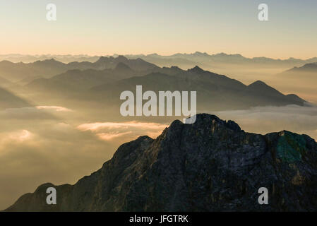 Sunrise, solar-flooded haze over Tyrol, background Hohe Tauern and Zillertaler alps, middle ground Karwendel with - Stock Photo