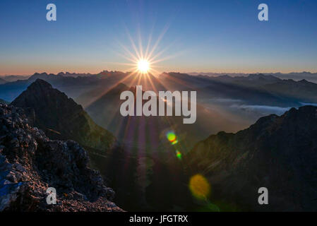 Sunrise and sunrays over the Karwendel with Arnspitzen in the middle ground, foreground Wetterstein Range, view - Stock Photo