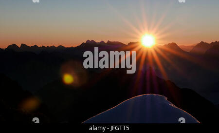 Sunrise and sunrays over the Karwendel with eastern Karwendel point and Birkkarspitze and Übersachallljoch and Bettelwurf, - Stock Photo