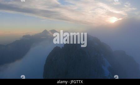 Sundown and diffuse light and fog, view of Schüsselkarspitze on rock Storm of the west ridge in Wetterstein Range, - Stock Photo