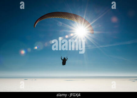 Paraglider about inversion layer in the blue heaven, aerial picture, the sun, ground fog, Bassano, Monte Grappa, - Stock Photo