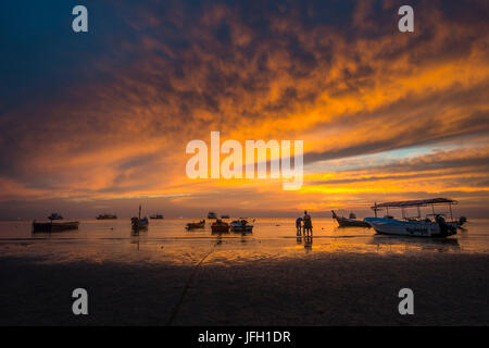 Family with small child on the beach in the water, boats in the sea at sundown, island Koh Tao, golf of Thailand, - Stock Photo