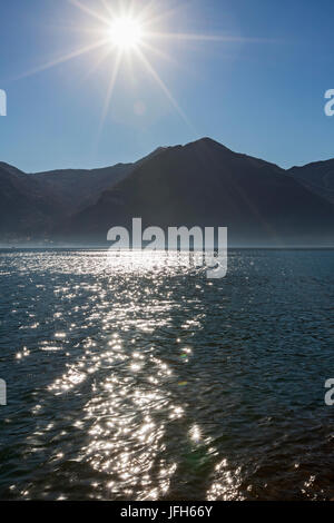 Scenic view of lake and silhouette of mountains - Stock Photo