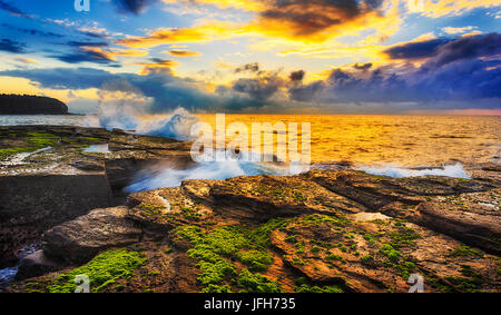 Warm colourful sunlight sheds on sandstone rocks and seaweed around eroded crack at sunrise time near Narrabeen - Stock Photo