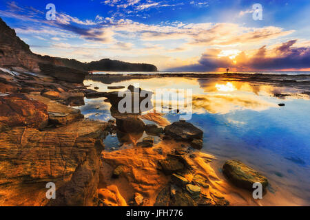 Reflection of clouds and rising sun in still salt water puddle during low tide sea bed opening near sandstone cliffs of Narrabeen headland in Sydney's