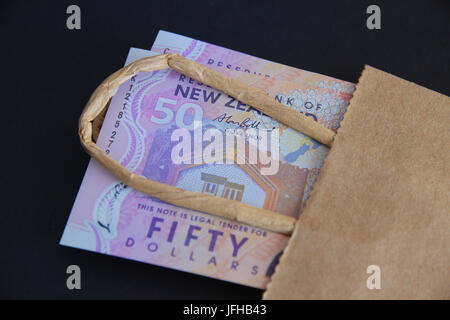 New Zealand fifty dollar notes in a bag. - Stock Photo