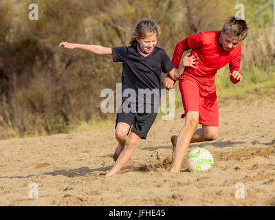 Girl and boy chasing soccer ball across sand - Stock Photo