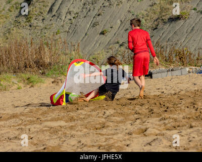 Girl scoring goal while playing soccer on the beach - Stock Photo