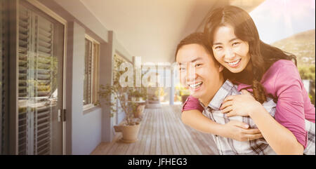 Composite image of man giving woman a piggyback - Stock Photo