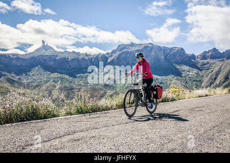 Woman riding electric bicycle on mountain road - Stock Photo
