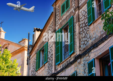 Buildings in the village of Valldemossa on the island of Majorca in Spain. In the background in the sky a passenger - Stock Photo
