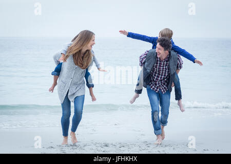 Happy mother and father carrying children at beach - Stock Photo
