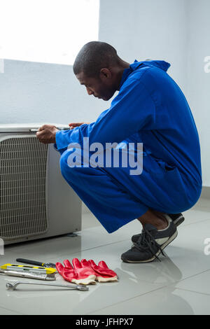 Handyman testing air conditioner with screwdrive - Stock Photo