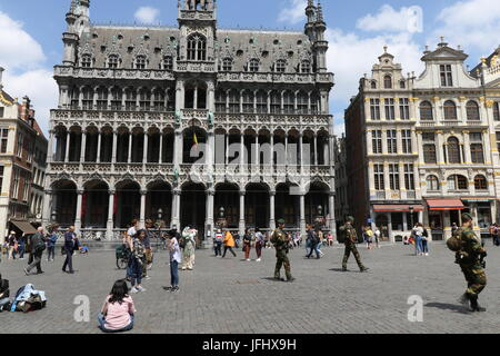 Armed soldiers guard Le Grand Place in Brussels with the Maison du Roi, House of the King, in the background. - Stock Photo
