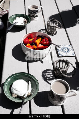 a white wooden table top with a healthy breakfast on it in the middle a brightly coloured bowl of fruit with strawberries, - Stock Photo