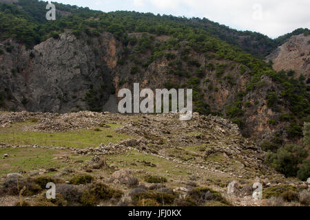 High above the steep walls of Aradena Gorge at Crete's South coast are the ruins of the former village Azogyres. - Stock Photo