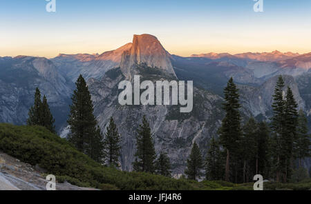The Half Dome is illuminated perfectly by the setting sun sun, the USA, California, Yosemite national park - Stock Photo