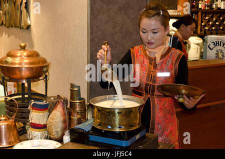 Mongolia, Central Asia, Ulaanbaatar / Ulan Bator, Mongolian cuisine, young woman while cooking - Stock Photo