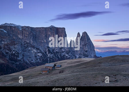 Europe, Italy, South Tyrol, Alpe di Siusi - Seiser Alm, Characteristic mountain barns with the peaks of Sciliar/Schlern - Stock Photo