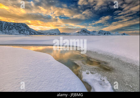 The golden sunrise reflected in a pool of the clear sea where the snow is almost melted, Haukland Lofoten Islands Norway Europe