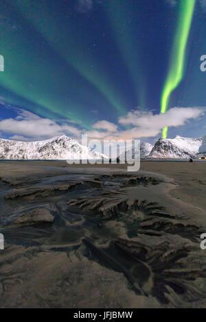 Northern Lights illuminate Skagsanden beach and the snowy peaks, Lofoten Islands Northern Norway Europe - Stock Photo