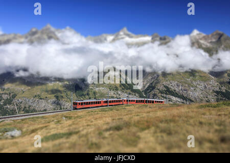 The Bahn train on its route with high peaks and mountain range in the background Gornergrat Canton of Valais Switzerland - Stock Photo