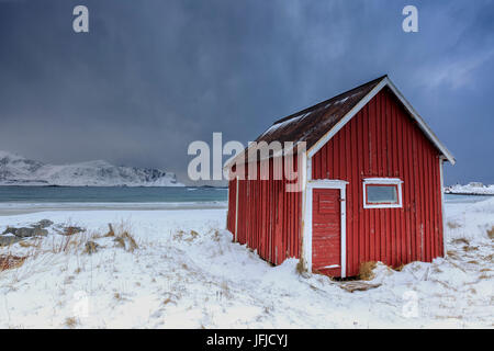 A typical house of the fishermen called rorbu on the snowy beach frames the icy sea at Ramberg Lofoten Islands Norway - Stock Photo