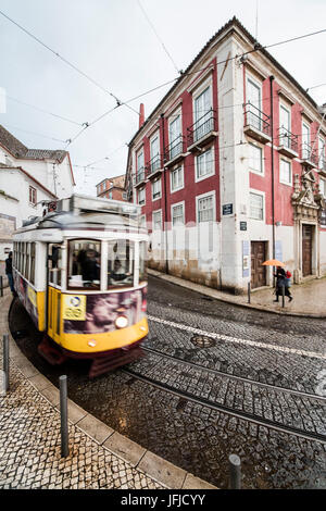 Yellow tram number 28 performs the longest route leading from centre of town up to the top of Alfama Lisbon Portugal - Stock Photo